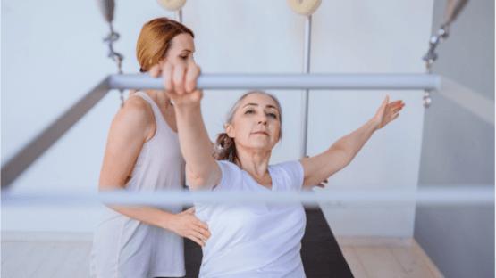 An elderly woman practicing pilates